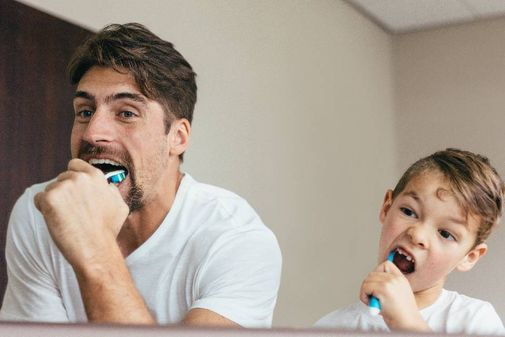 father and son doing teeth cleaning